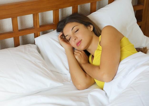 Donna brasiliana che dorme nel letto in comode lenzuola bianche a casa