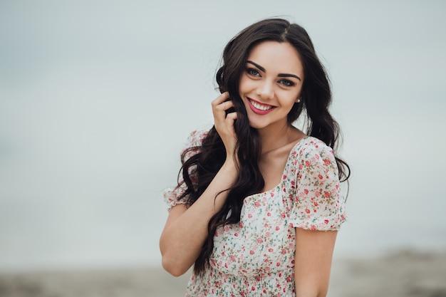 Donna bruna che indossa un vestito floreale