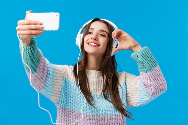 Donna bruna con auricolari prendendo selfi