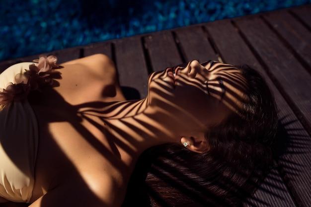 Donna bruna con gli occhi chiusi sotto una palma a bordo piscina