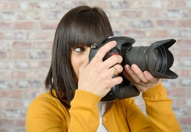 Donna bruna con macchina fotografica