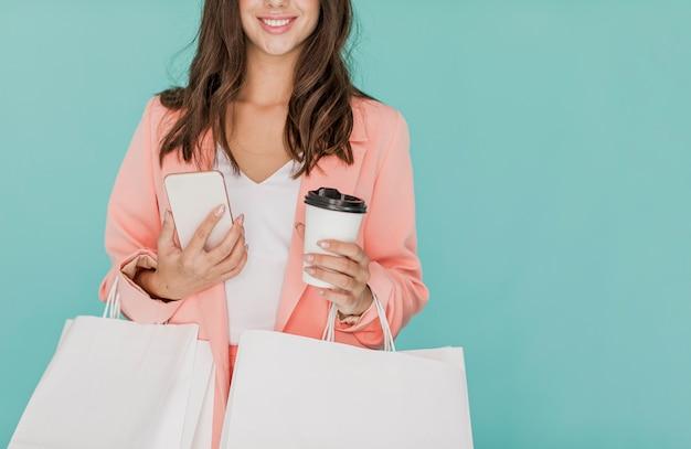 Donna bruna con smartphone e caffè
