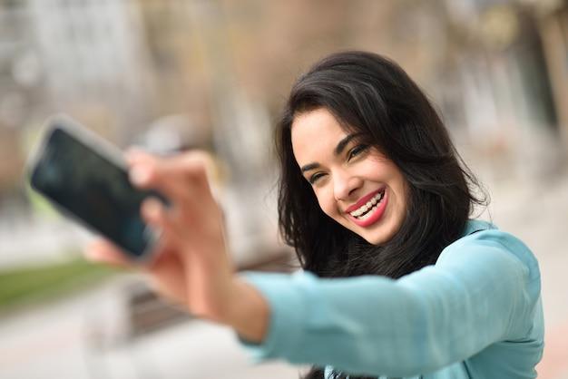Donna bruna con un grande sorriso di scattare una foto
