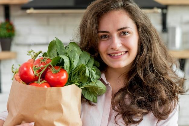 Donna bruna con un sacchetto di carta pieno di cibo sano