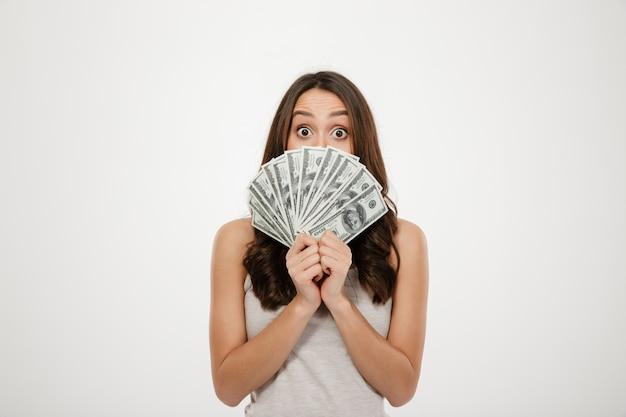 Donna bruna eccitata che copre il viso con un fan di banconote in dollari, esprimendo shock e sorpresa sul muro bianco