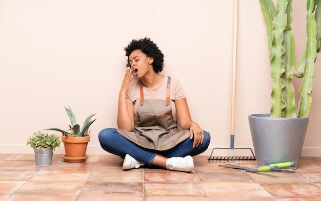 Donna bruna giardiniere seduta sul pavimento