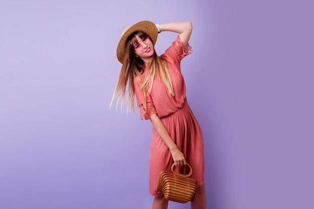 Donna bruna in abito rosa alla moda e cappello di paglia tenendo borsa di bambù su viola.