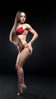 Donna bruna in posa in un bikini rosso