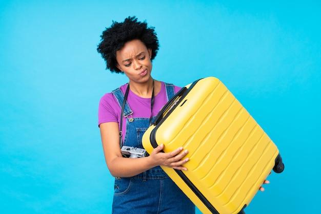 Donna bruna in possesso di una valigia su sfondo blu isolato