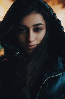 Donna bruna in una giacca con cappuccio