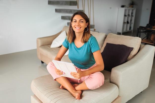 Donna bruna trascorrere del tempo a casa, utilizzando la tavoletta, guardando video online