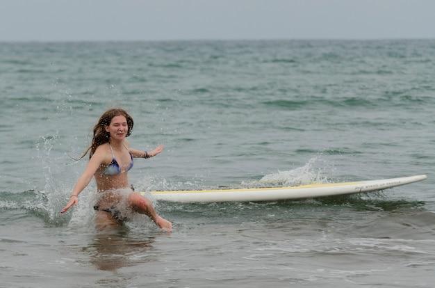 Donna caduta da una tavola da surf nel mare, sayulita, nayarit, messico