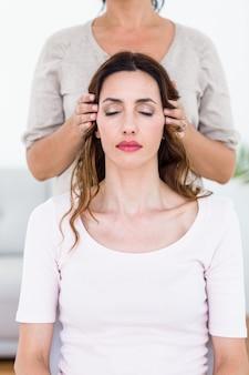 Donna calma che riceve il trattamento di reiki