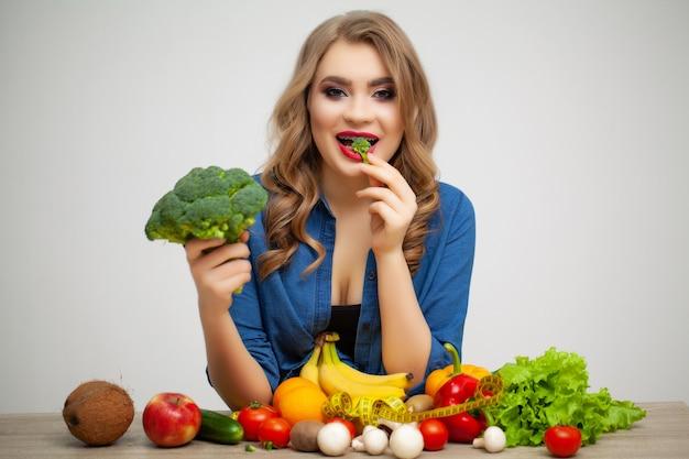 Donna carina a un tavolo in possesso di un broccoli su uno sfondo di frutta e verdura