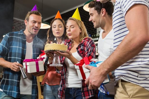 Donna carina che soffia le candeline di compleanno con un gruppo di amici