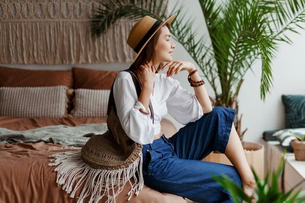 Donna carina con i capelli corti rilassante nella sua camera da letto, stile boho, palme e macramè sulla parete