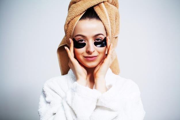 Donna carina in bagno usa patch per la cura della pelle del viso.