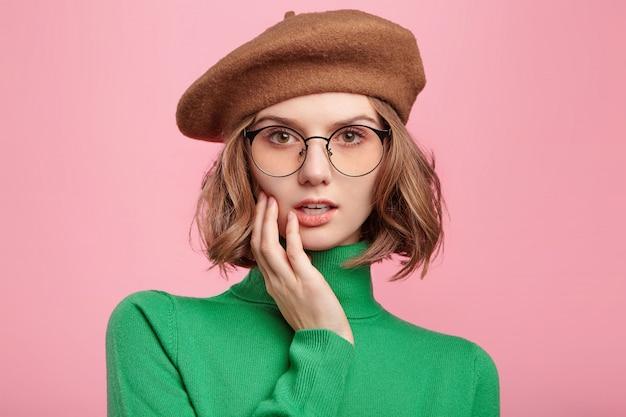Donna carina in berretto e maglione a collo alto