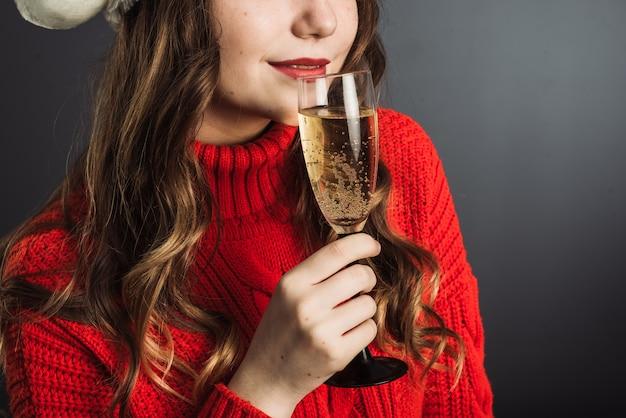 Donna carina in maglione rosso celebra il natale e beve champagne da un bicchiere