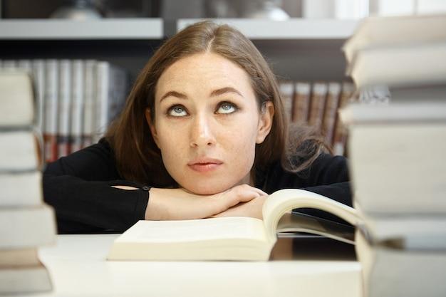 Donna carina studentessa bruna in giacca nera studiando e leggendo il libro di testo o manuale nella biblioteca universitaria ma avendo difficoltà a capire il materiale, alzando gli occhi, guardando annoiato e confuso