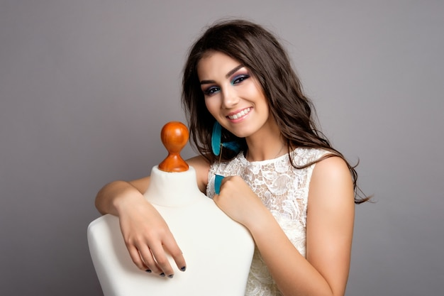 Donna castana abbastanza giovane in vestito bianco che abbraccia manichino, ritratto sorridente dello studio su fondo grigio, ritratto sorridente della sposa