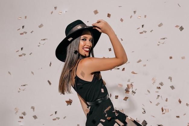 Donna castana allegra che tiene il suo cappello e che salta sopra la parete isolata. ragazza spensierata che gode dei coriandoli intorno e buon umore alla festa