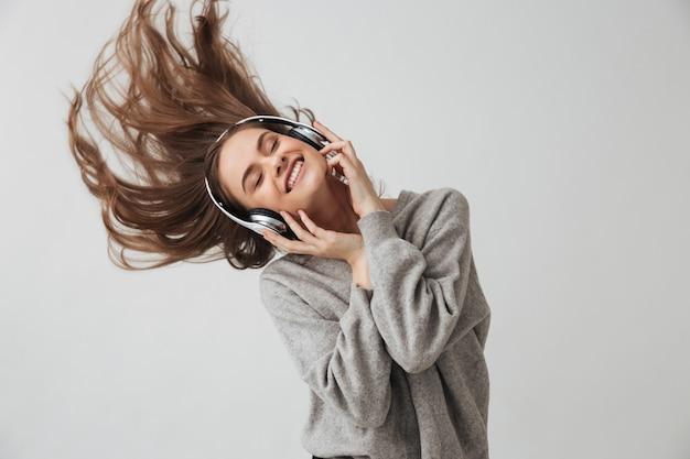 Donna castana allegra in maglione e cuffie che ascolta musica con gli occhi chiusi sopra il muro grigio