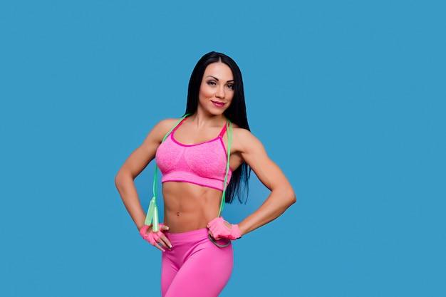 Donna castana allegra negli abiti sportivi rosa con il salto della corda