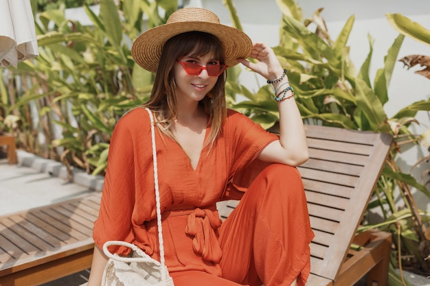Donna castana apparente in attrezzatura arancio alla moda e cappello di paglia che si rilassano sullo sdraio vicino allo stagno.