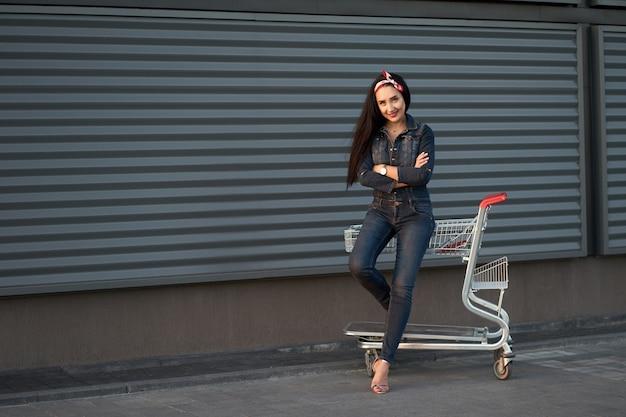 Donna castana attraente alla moda con capelli lunghi e la bandana rossa