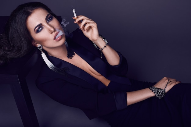 Donna castana calda elegante che fuma una sigaretta