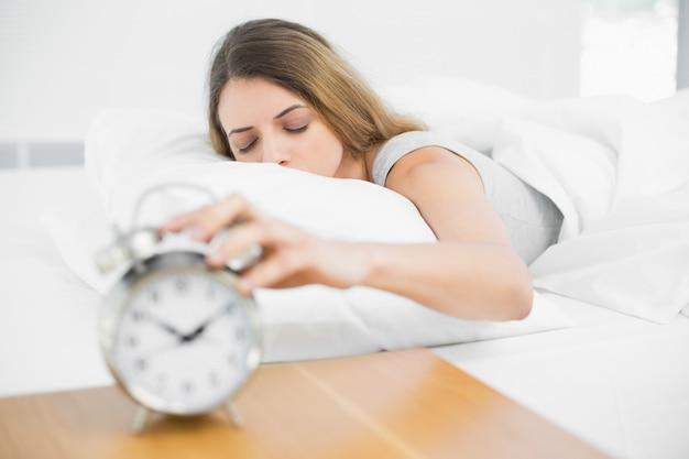 Donna castana calma che si trova sul suo letto con gli occhi chiusi