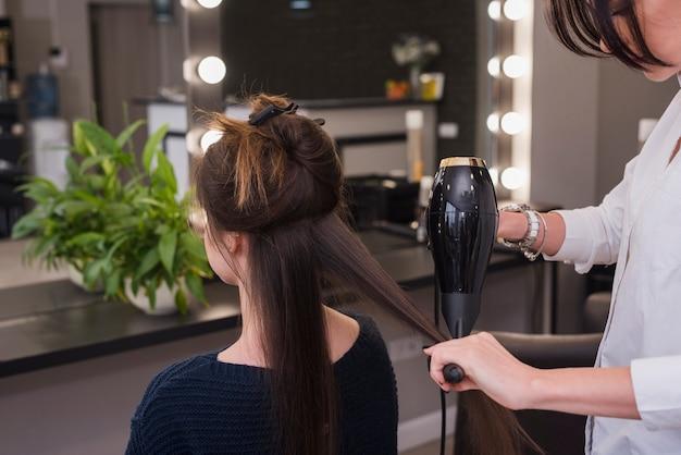 Donna castana che fa i suoi capelli fatti