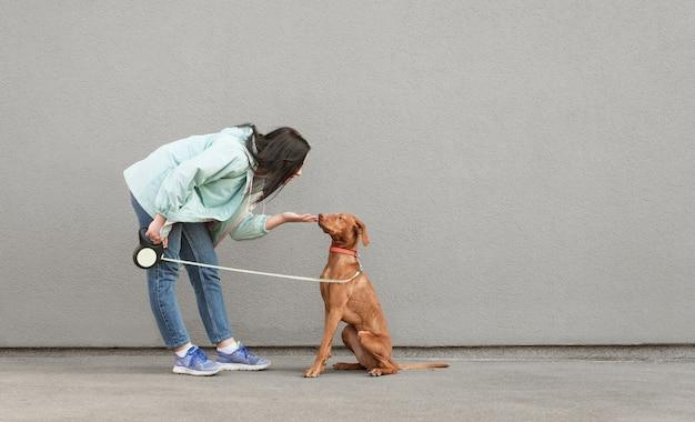 Donna castana che gioca con un bel giovane cane
