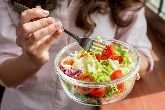 Donna castana che mangia un'insalata