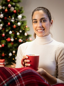 Donna castana che tiene una tazza rossa