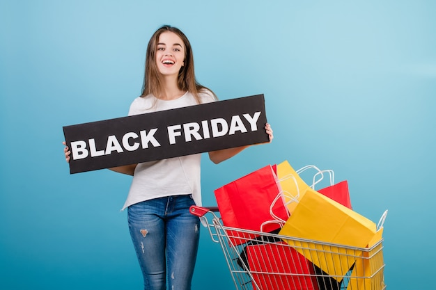 Donna castana con il carrello di acquisto pieno di sacchi di carta rossi e gialli variopinti e del segno di venerdì nero isolati sopra il blu