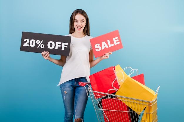 Donna castana con il carrello di acquisto pieno di sacchi di carta rossi e gialli variopinti e segno di vendita del 20% isolato sopra il blu