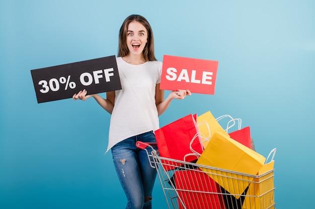 Donna castana con il carrello di acquisto pieno di sacchi di carta rossi e gialli variopinti e segno di vendita del 30% isolato sopra il blu
