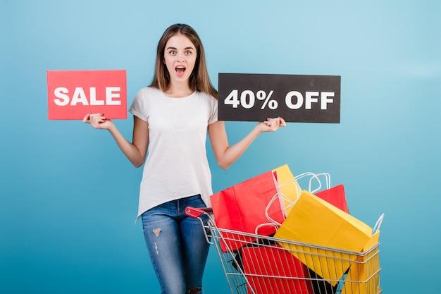 Donna castana con il carrello di acquisto pieno di sacchi di carta rossi e gialli variopinti e segno di vendita del 40% isolato sopra il blu