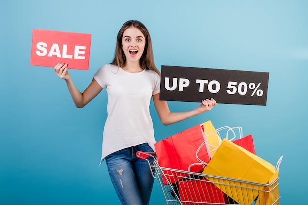 Donna castana con il carrello di acquisto pieno di sacchi di carta rossi e gialli variopinti e segno di vendita del 50% isolato sopra il blu