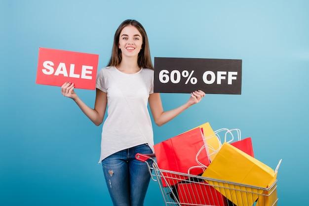 Donna castana con il carrello di acquisto pieno di sacchi di carta rossi e gialli variopinti e segno di vendita del 60% isolato sopra il blu