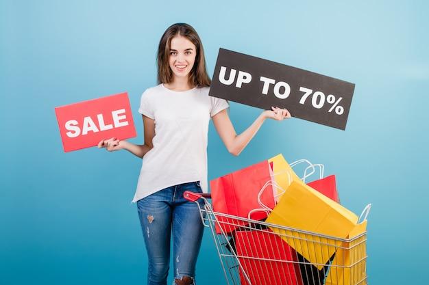 Donna castana con il carrello di acquisto pieno di sacchi di carta rossi e gialli variopinti e segno di vendita del 70% isolato sopra il blu