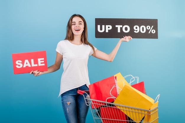 Donna castana con il carrello di acquisto pieno di sacchi di carta rossi e gialli variopinti e segno di vendita del 90% isolato sopra il blu