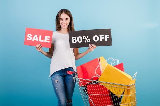 Donna castana con il carrello di acquisto pieno di sacchi di carta rossi e gialli variopinti e segno di vendita dell'80% isolato sopra il blu