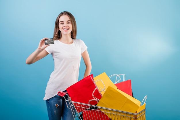 Donna castana con il carrello pieno dei sacchi di carta variopinti e della carta di credito isolata sopra il blu