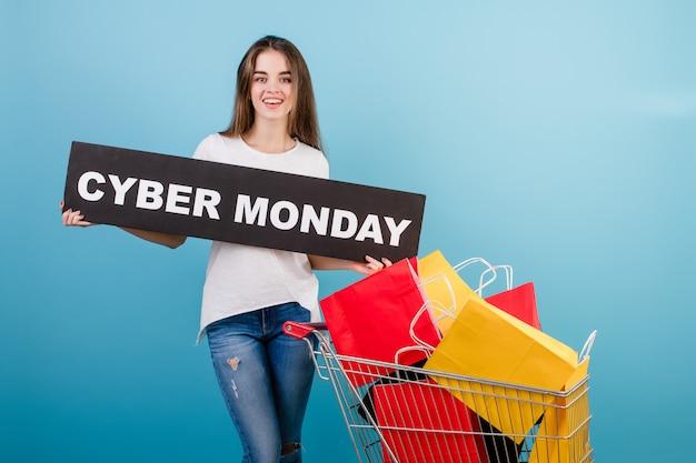 Donna castana con il carrello pieno di sacchi di carta rossi e gialli variopinti e segno cyber di lunedì isolato sopra il blu