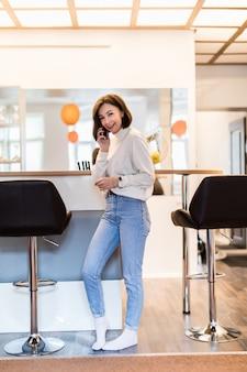 Donna castana con il telefono che sta nella cucina panoramica in abbigliamento casual
