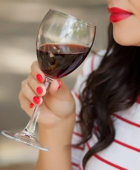 Donna castana con le labbra rosse che beve vino rosso in caffè all'aperto