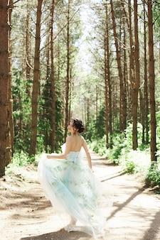 Donna castana con un bel vestito che corre nella foresta